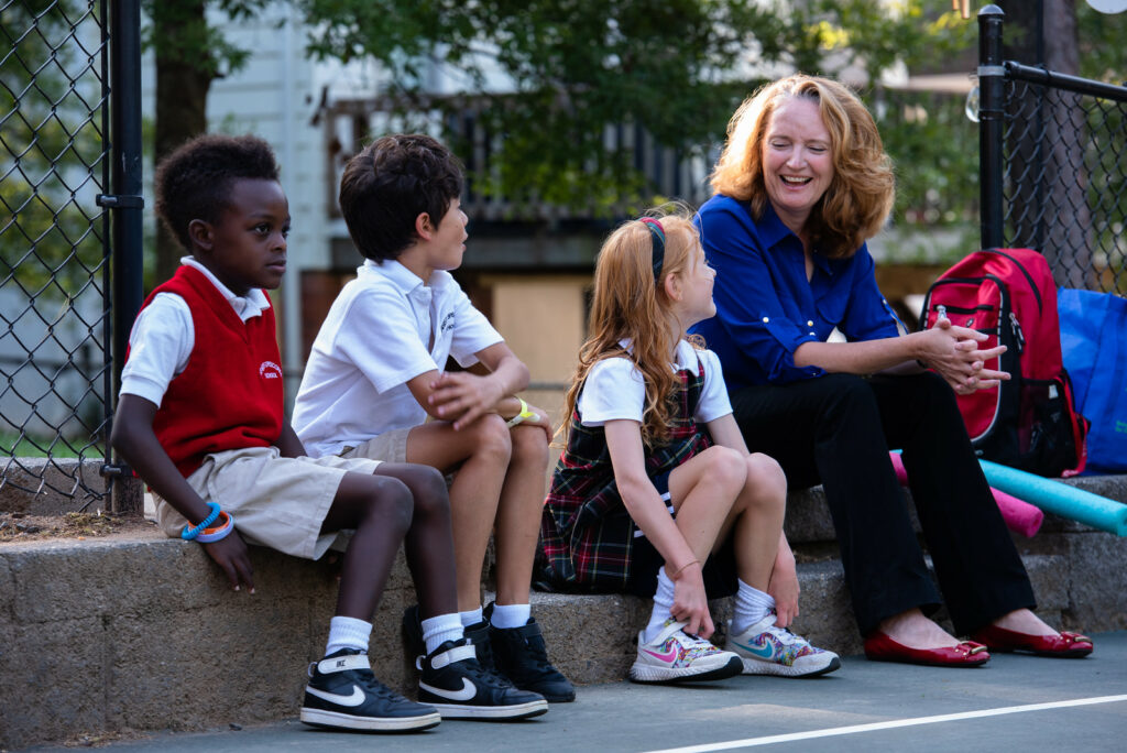 head of school sitting with students at PE